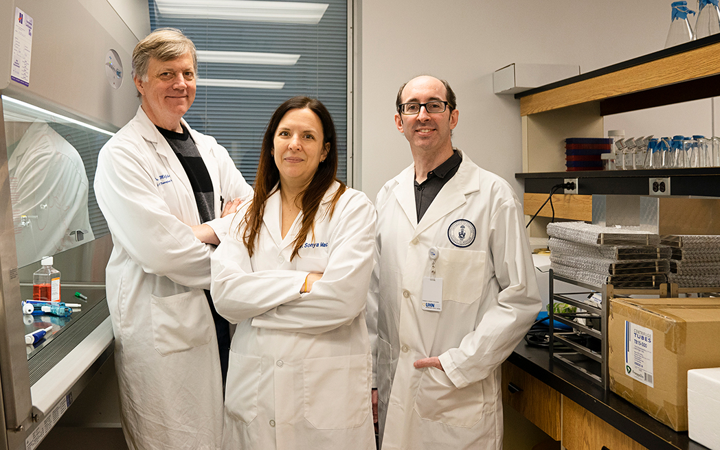 Ian McGilvray, Sonya MacParland, and Gary Bader in lab coats. Photo taken in a lab.