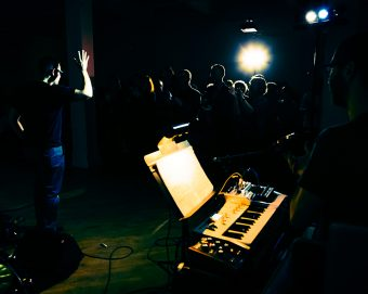 Eliot Britton standing in spotlight with one arm raised in a darkly lit space, where the outline of an audience is visible in the background and a keyboard is under spotlight in the foreground