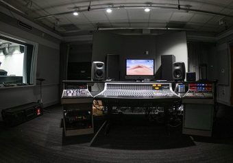 Dimly lit studio space with track lights shining on the electronic music equipment, speakers and large monitor screen underneath; on the left is a window looking into another brightly lit studio room