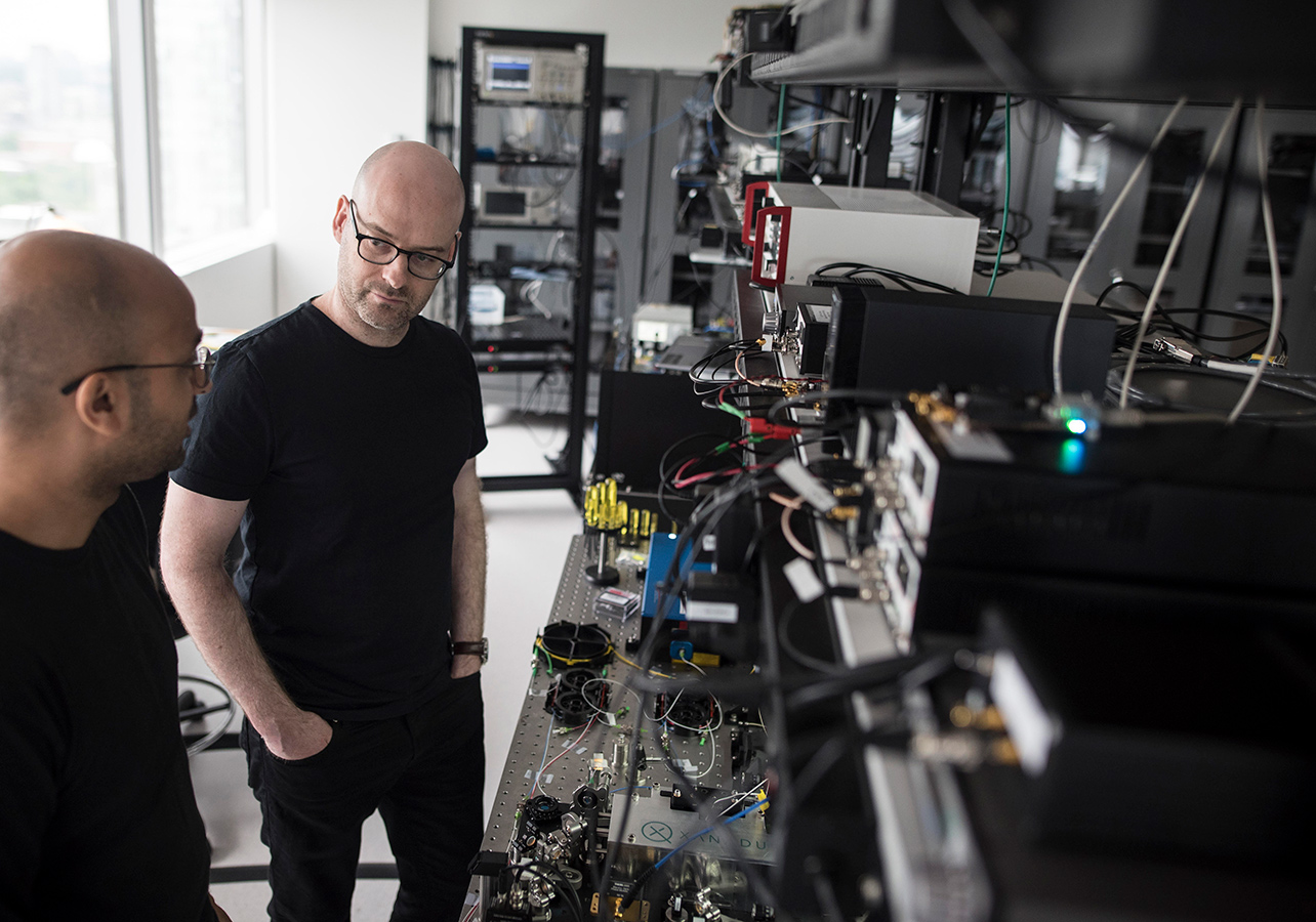 Christian Weedbrook standing in front of quantum computers and listening as Varun Vaidya discusses the working principle of one of the building blocks of quantum computers at their Toronto office