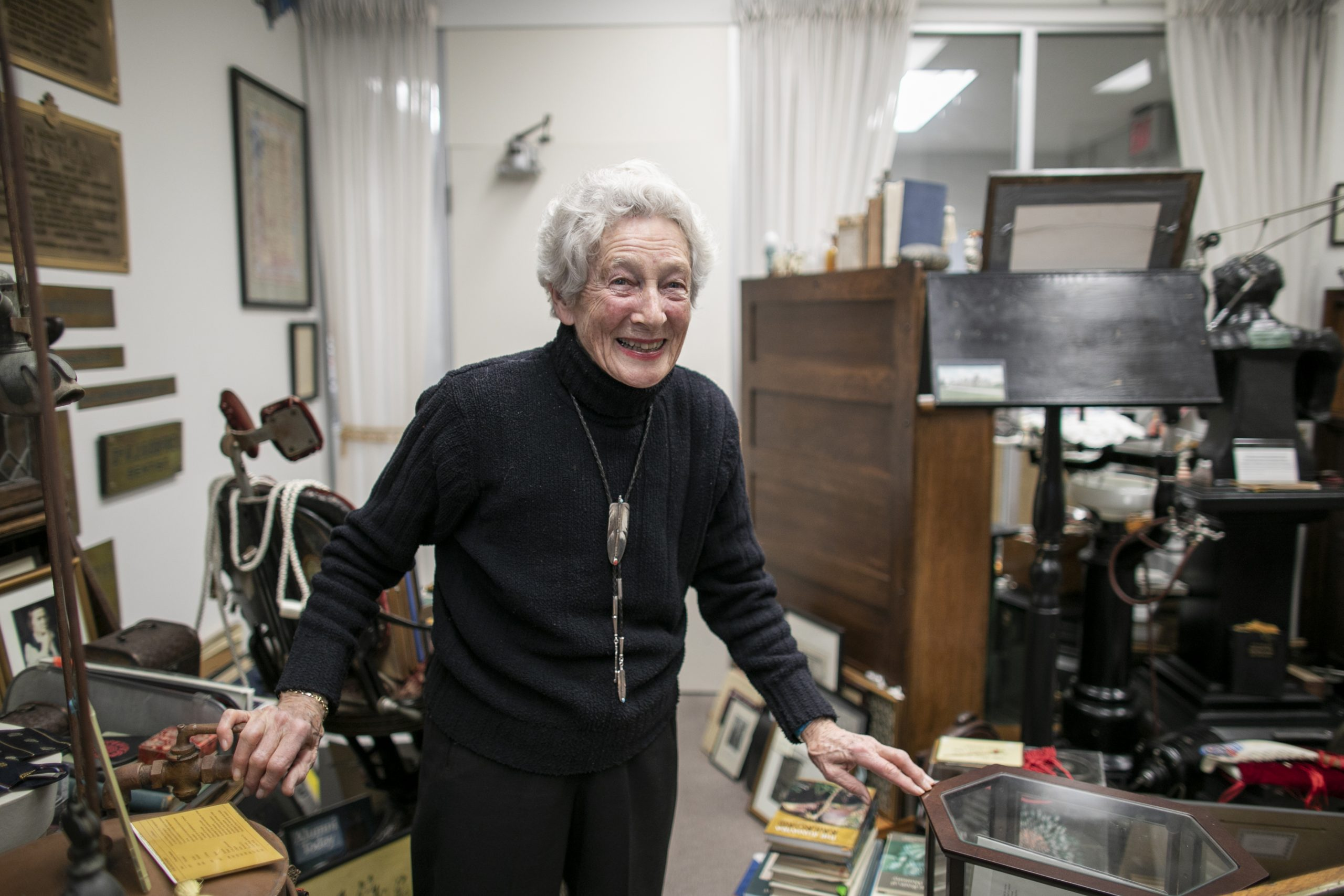 Dr. Anne Dale smiling and standing in a room cluttered with objects