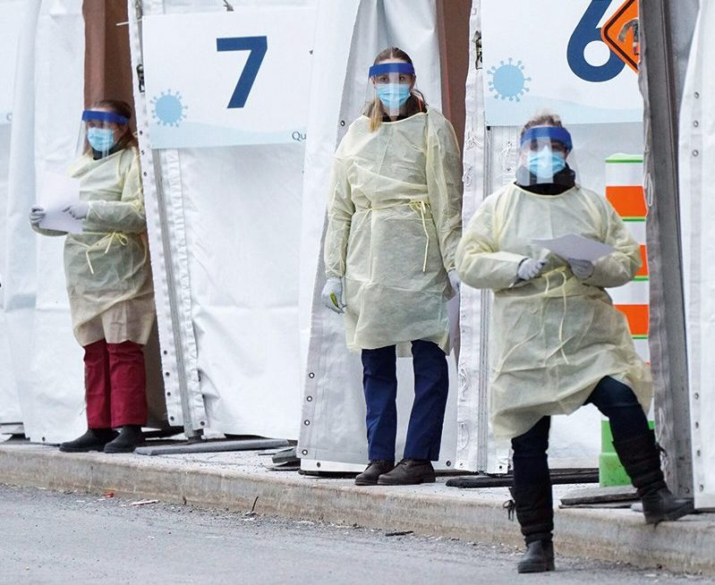 "Three health-care workers wearing masks with shield and white gowns and gloves are standing outside white tents labelled ""6"" and ""7"""