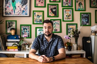 Writer and U of T grad Aaron Hagey-Mackay sits at a desk in his home. On the wall behind him hang many framed comic book covers.