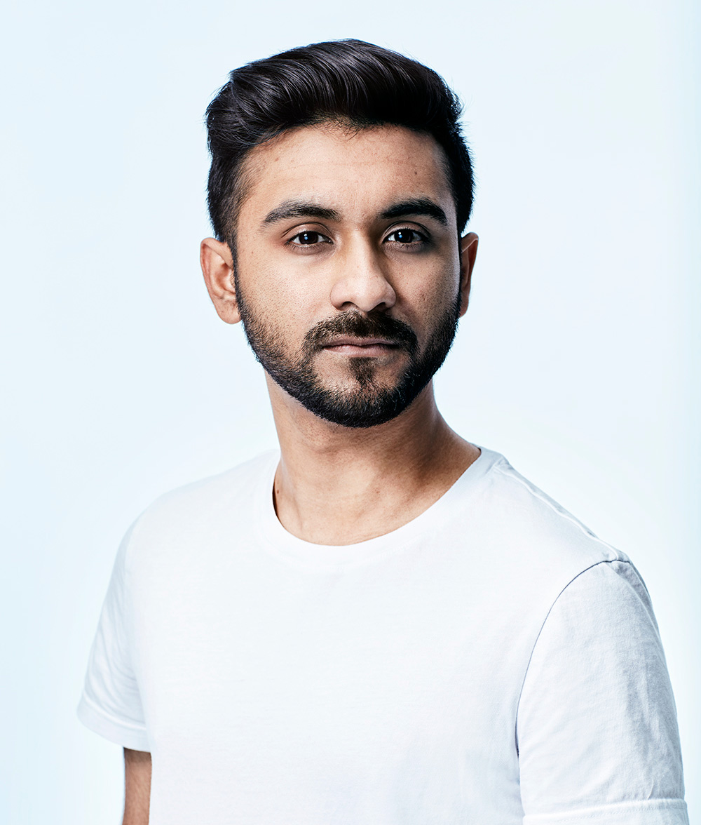 Photo of Tahmid Khan in a white T-shirt looking at the camera with a serious expression, shot in a studio against a bluish white background