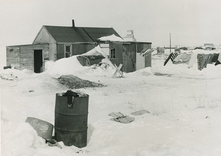 Black and white photo of a house surrounded by snow-covered ground, with a steel drum barrel in the foreground.