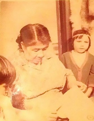 Sepia-toned photo of an older woman sewing, with a young girl wearing a headband to the right and Brenda Wastasecoot as the little girl on the left watching the woman's hands