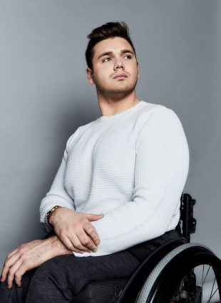 Headshot of George Alevizos with the upper part of his wheelchair visible