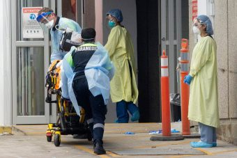 Paramedics wearing protective equipment wheel a patient into a hospital emergency department
