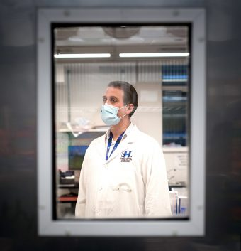 Photo of U of T and Sunnybrook Health Sciences Centre clinical microbiologist Robert Kozak wearing a lab coat and a mask, taken through a small window in a door of a lab