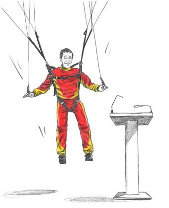 Prof. Daniel Zingaro, wearing a red and yellow jumpsuit, in a parachute harness, floating toward a lectern