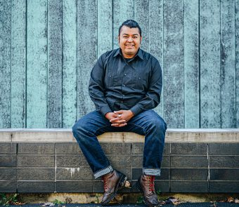 Prof. Jerry Flores smiling and sitting on a bench outside with the blue wooden walls of a building behind him