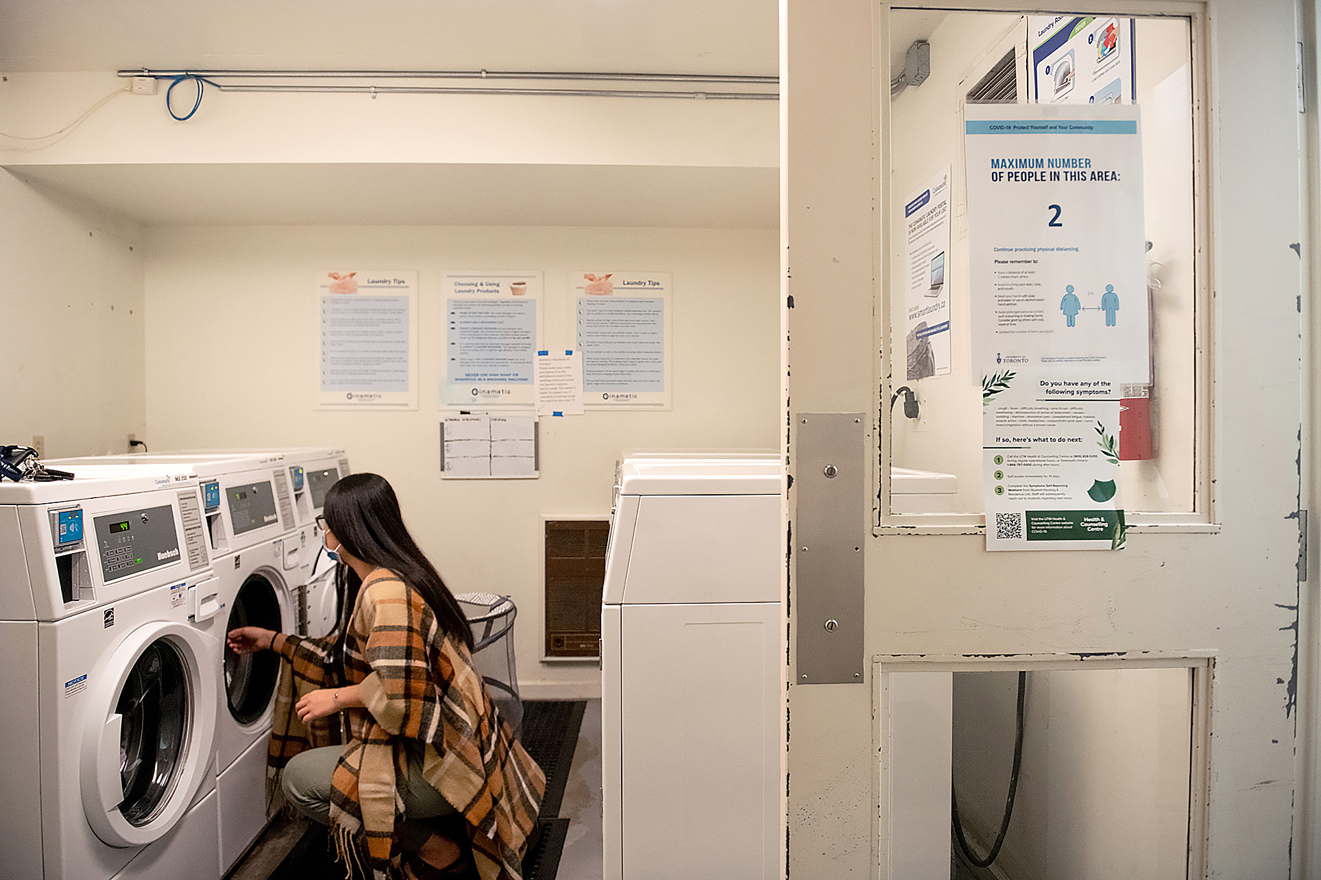 Shirley Liu crouched in front of washing machine in a laundry room with a sign on the door indicating a maximum of two people allowed in the area