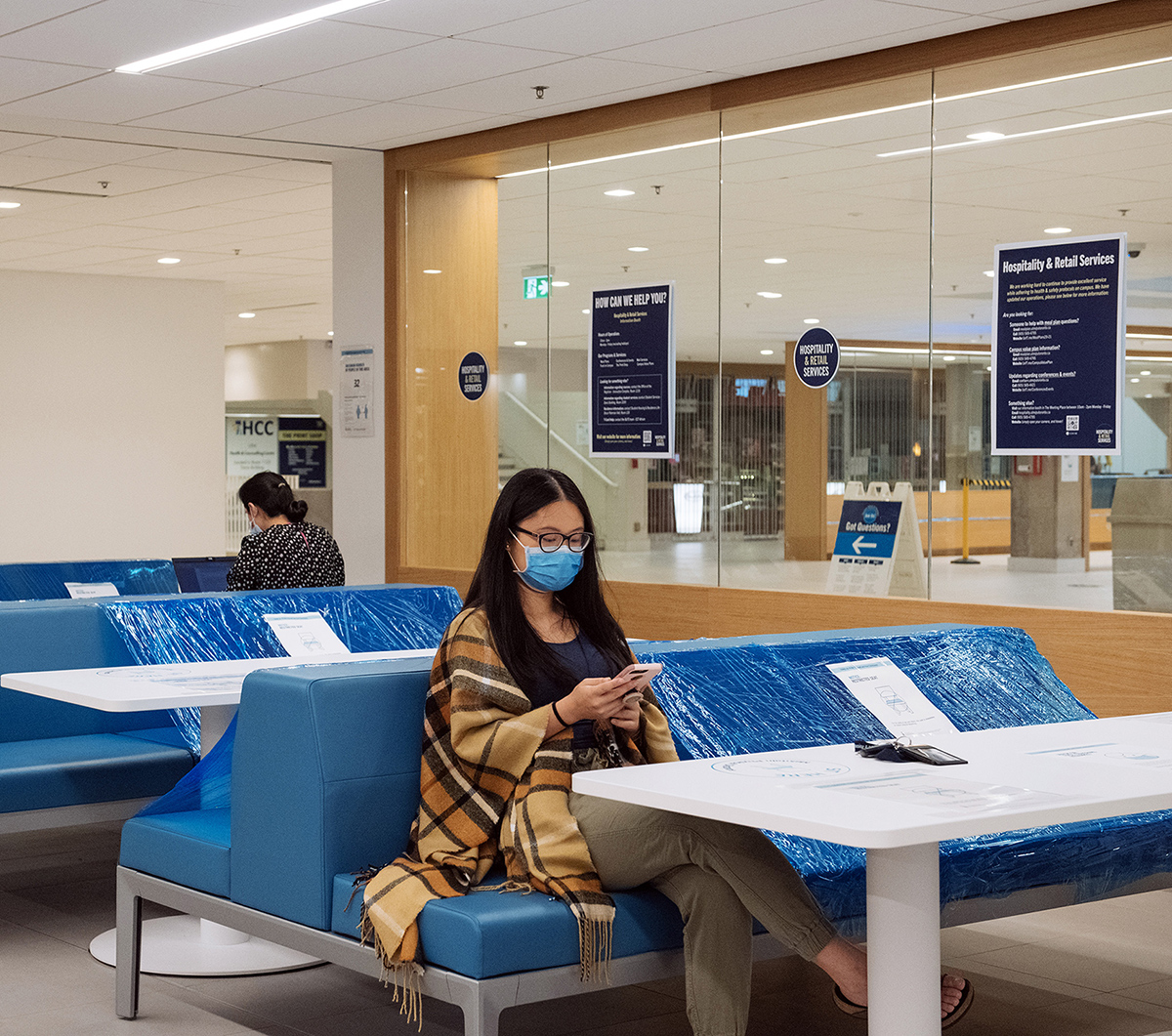 Shirley Liu in a student lounge, looking at her phone while sitting on a blue bench half-covered with plastic wrap