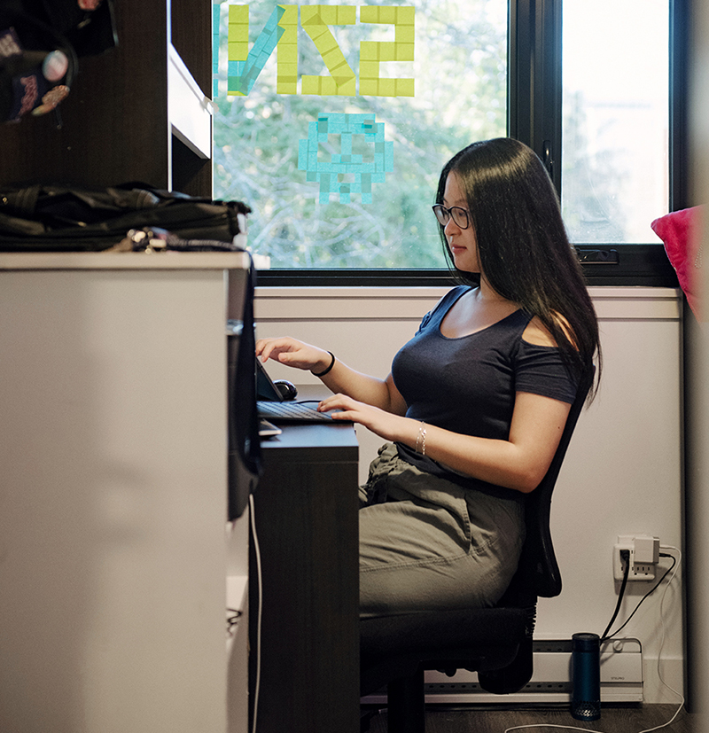 Shirley Liu sitting at her desk, typing on her keyboard