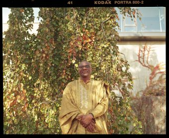U of T Scarborough Principal Wisdom Tettey standing in front of vines of leaves by the side of a building.