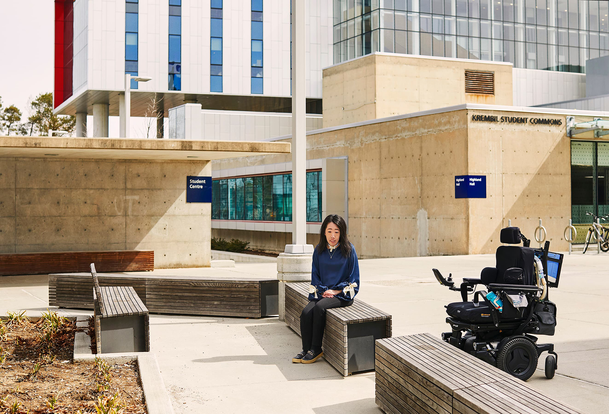 Emily Chan sitting on a bench outside UTSC's Krembil Student Commons, with her wheelchair next to her