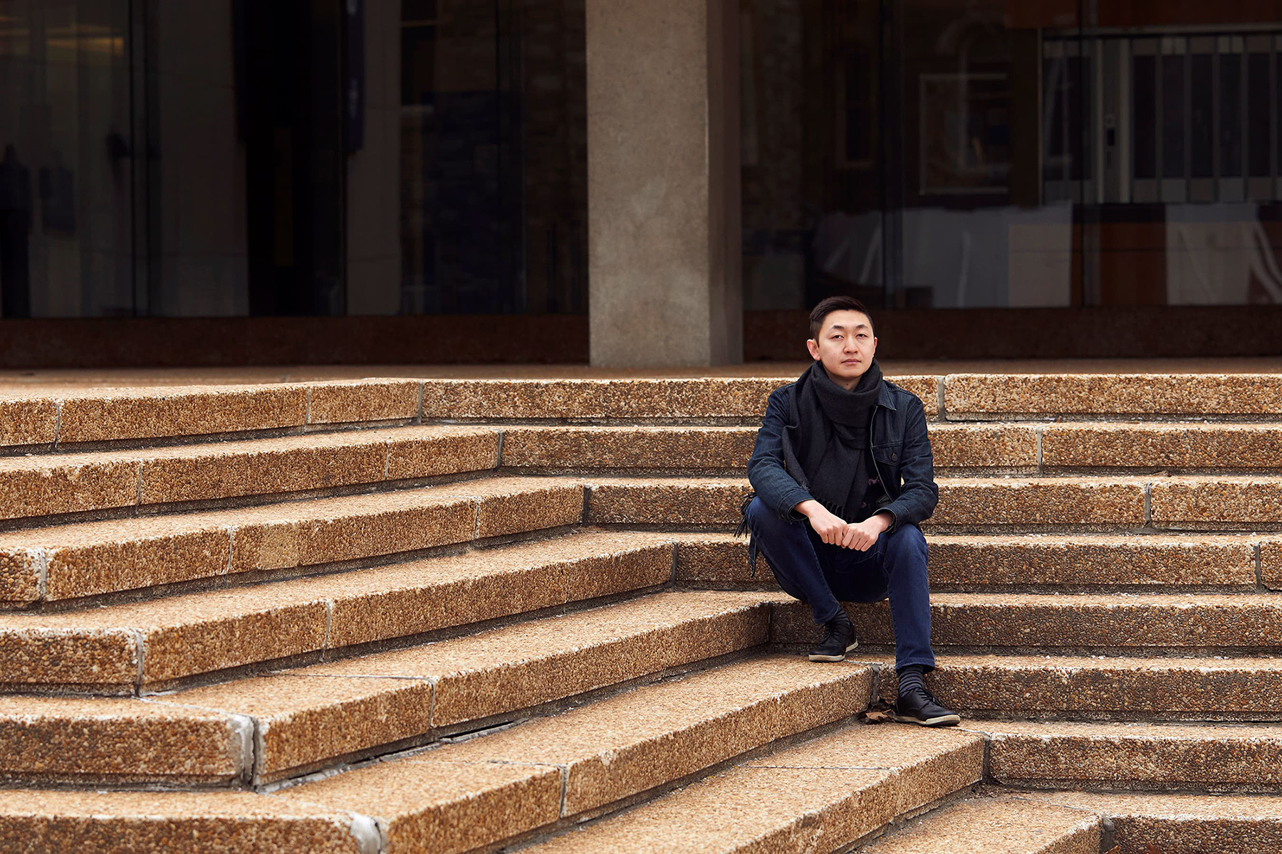 Alex Lu sitting on stone steps outside a campus building