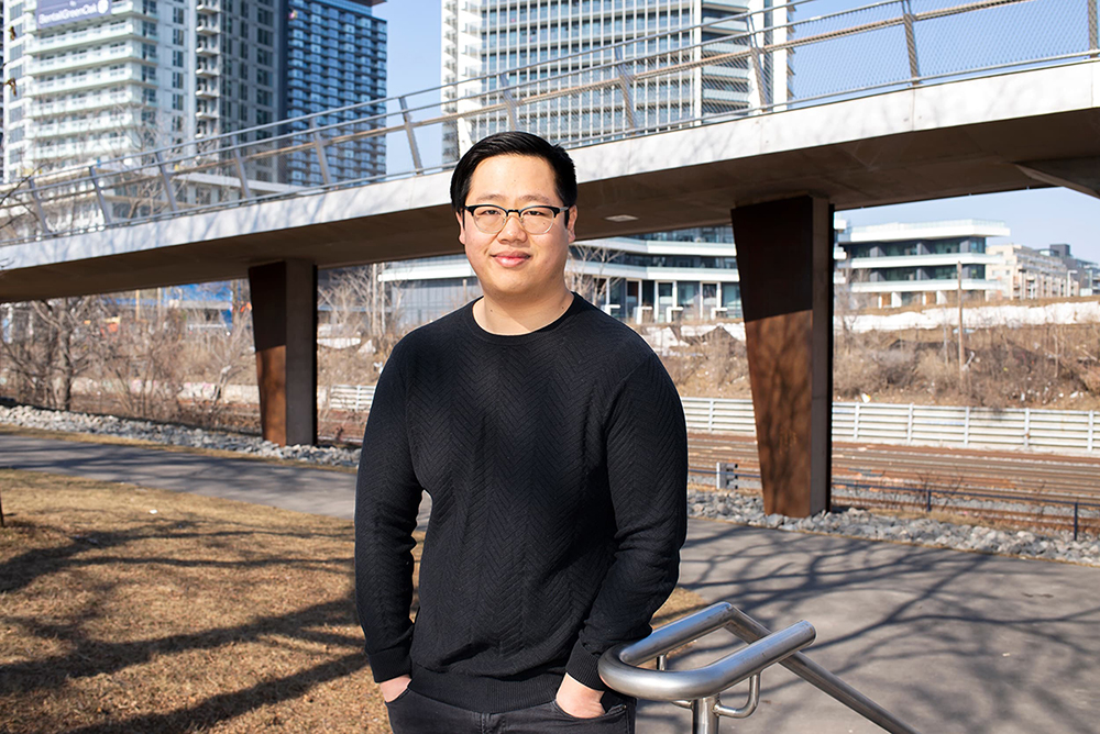 Outdoor photo of Austin Yeh with a bridge and residential buildings in the background