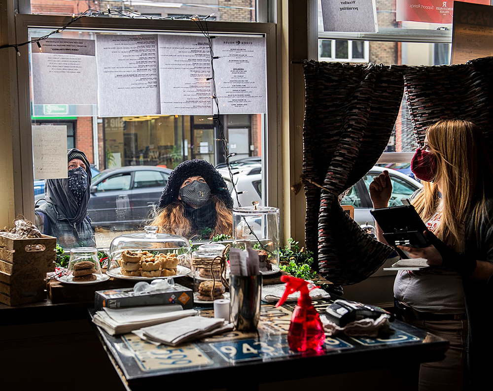 Photo of customers looking at paper menus outside the window of Cider House