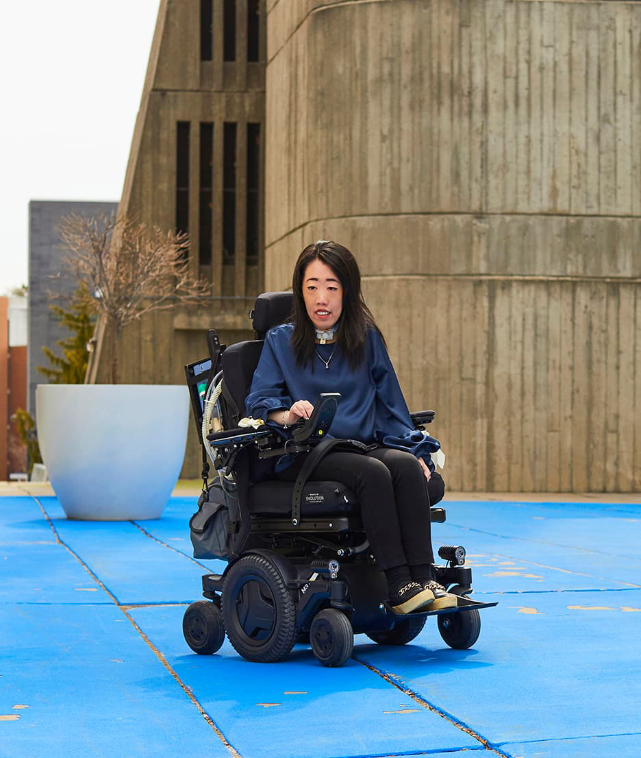 Emily Chan sitting in her wheel chair outdoors on the UTSC campus