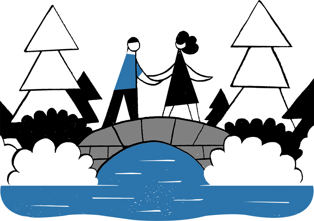 A man and woman holding hands and standing on a bridge over water