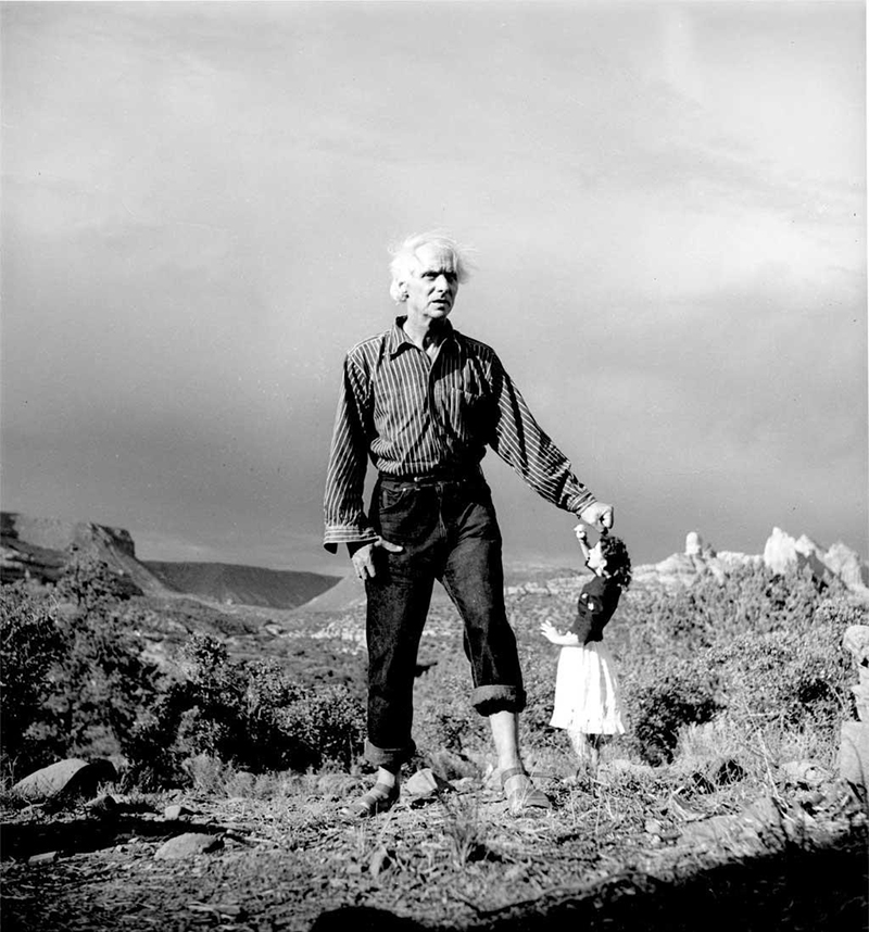 Black and white photo of a giant-sized man standing on a grassy landscape beside a miniature-sized woman looking up at him