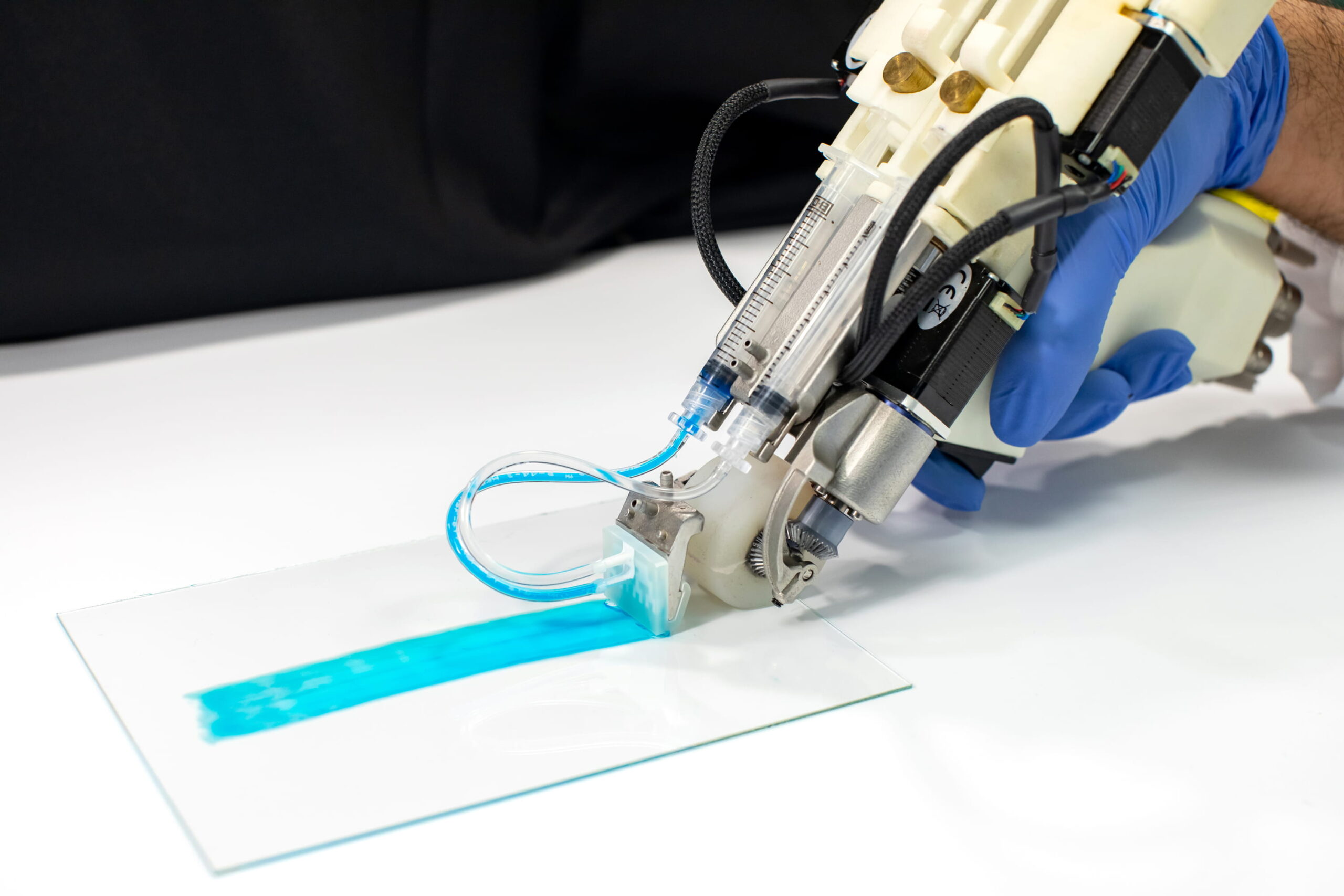 A device with a small roller applies a blue liquid along a smooth glass surface