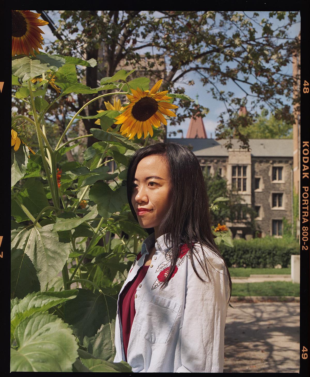 Jialiang Zhu standing next to a sunflower patch