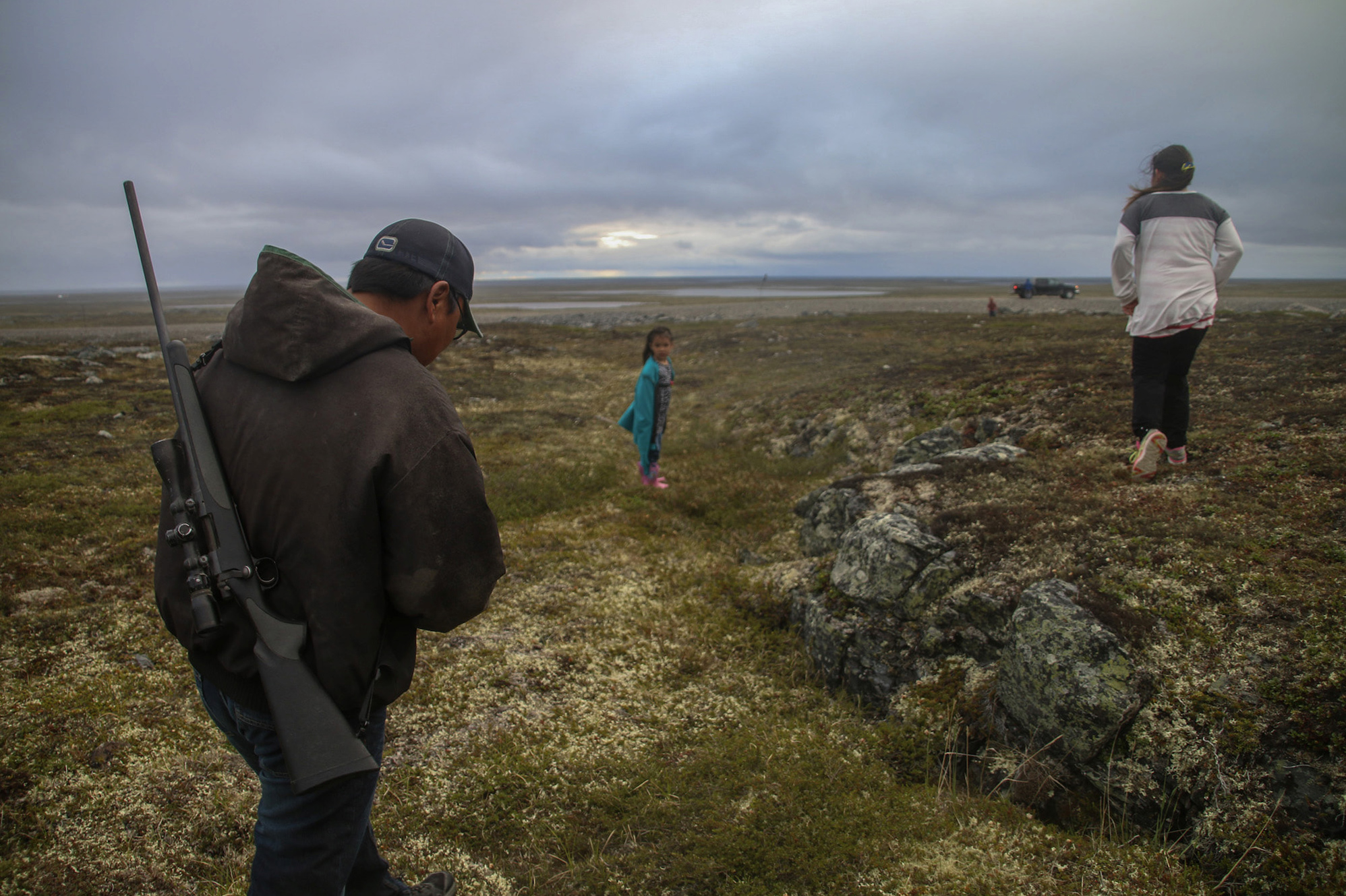 A man with a gun strapped to his back, a woman, and a young girl walking across a field toward a vehicle in the distance