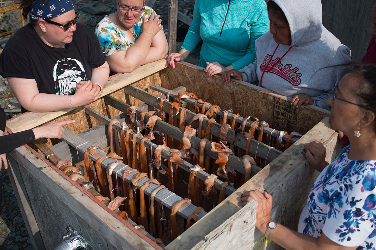 A group of women gathered around a smoker with strips of fish on racks inside
