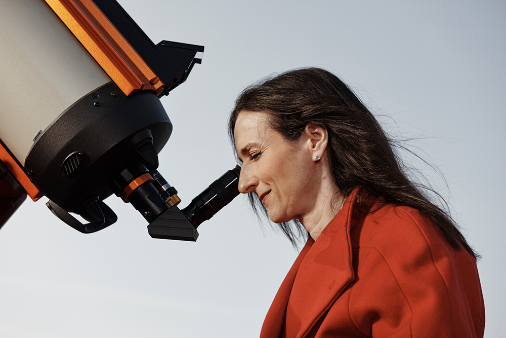 Sara Seager, who has dark hair and is wearing a red coat, is in profile, peering through the eyepiece of a telescope