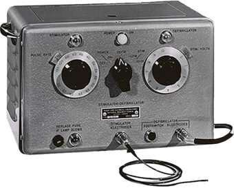 Black and white photo of the first electronic heart pacemaker, a metal box with three black dial in the centre and connectors at the bottom