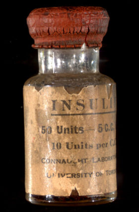 """An old vial of insulin with a cracked red stopper and a frayed label that reads """"INSULIN 50 Units-5 C.C. 10 Units per C.C. Connaught Laboratories University of Toronto"""""""